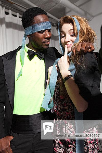 Paar auf Party  Mann mit Streamer für Augen