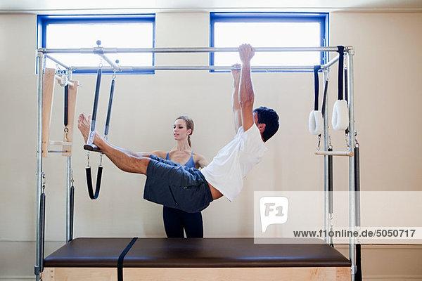 Mann beim Pilatespielen mit Instruktor
