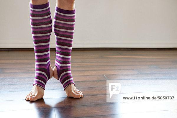 Frau trägt gestreifte Beinlinge auf den Zehenspitzen
