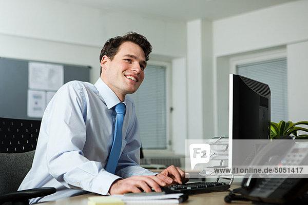 Büroangestellter am Schreibtisch sitzend  lächelnd