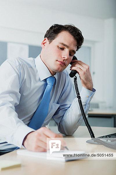 Büroangestellter beim Telefonieren  Schreiben im Notizbuch