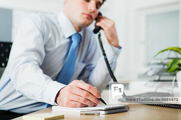 Büroangestellter auf Anruf  in Notizbuch schreiben