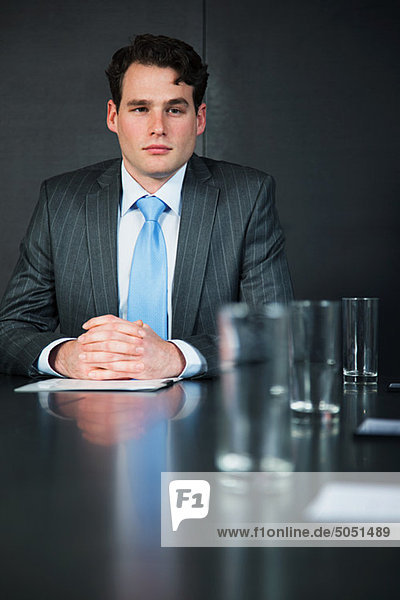 Kaufmann im Konferenzraum mit Dokumenten