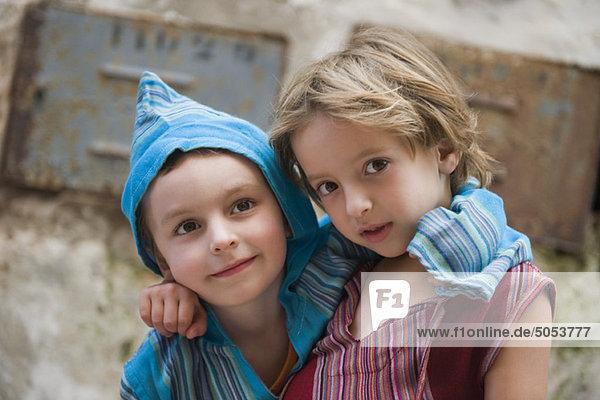 Junge Geschwister mit Armen um die Schultern  Portrait