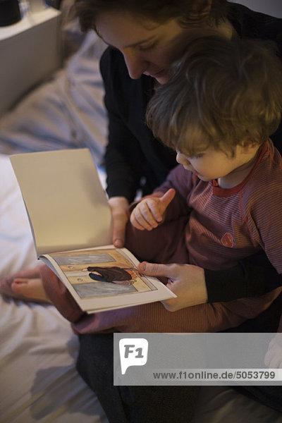 Mutter hält Kleinkind-Sohn auf Schoß  liest Gutenachtgeschichte