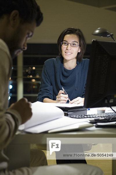 Kollegen  die nachts im Büro gemeinsam am Projekt arbeiten