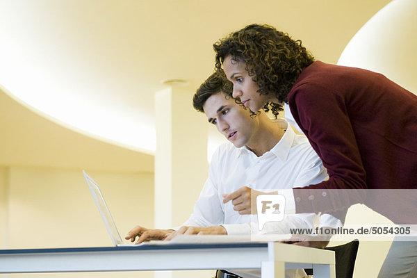 Kollegen  die gemeinsam einen Laptop benutzen