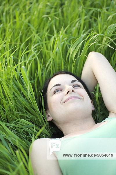 Portrait einer jungen Frau im Gras liegend