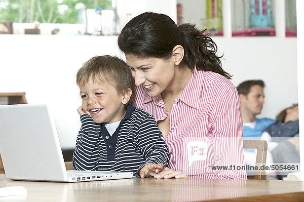 Mutter und Sohn am Tisch in Fron der Laptop-computer