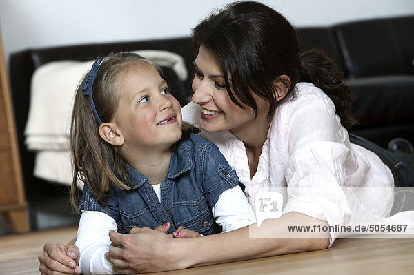 portrait of mother and young daughter lying on floor at home