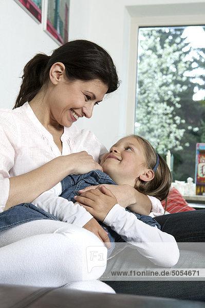 junge Frau und Tochter auf Sofa Spaß