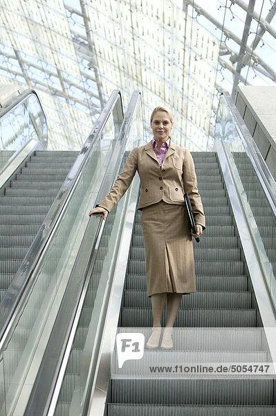 Geschäftsfrau auf Rolltreppe