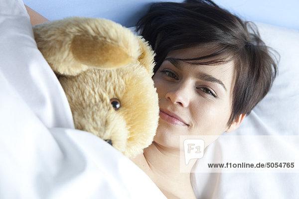 Portrait of young Woman liegend im Bett mit Kuscheltier
