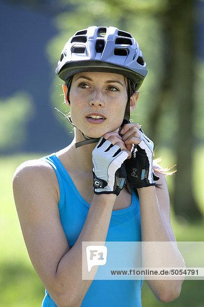 Porträt von weiblichen Radrennfahrer anpassen ihren Helm