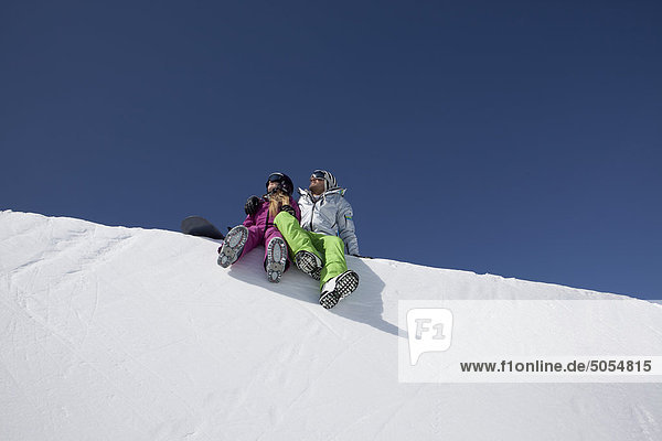 Snowboarder paar sitzen auf Schnee