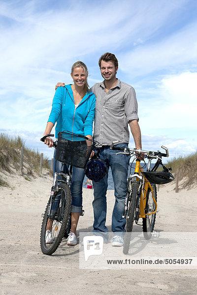 Porträt jungen Paares mit Fahrrädern am Strand