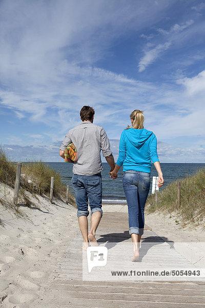 junges paar hin zum Strand gehen hand in hand