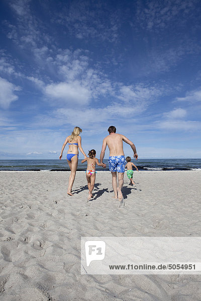 young family on beach running towards the sea
