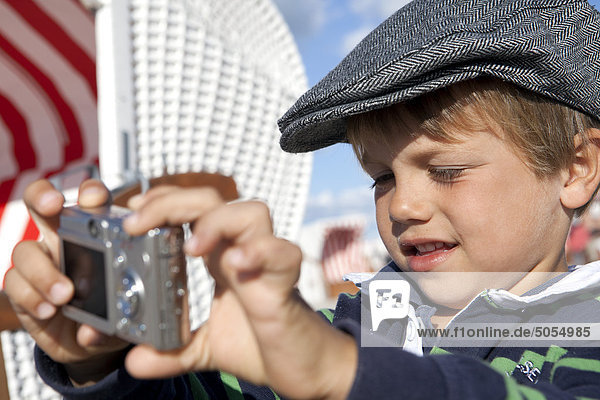 portrait of young boy taking self-portrait with digital camera