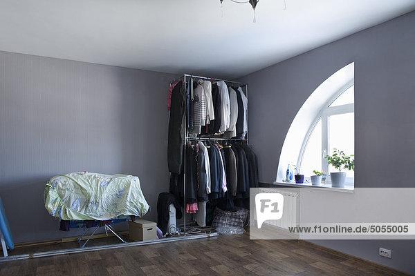Blick in Zimmer mit Kleidung in offene Schrank