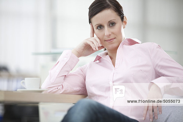 Porträt der jungen geschäftsfrau sitzt am Tisch