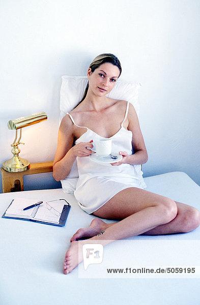 Frau gewundener auf einem Bett Tee trinken