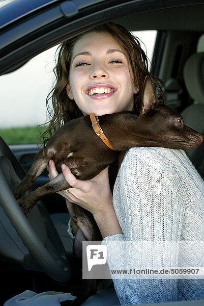 Portrait einer Frau in Auto mit Hund