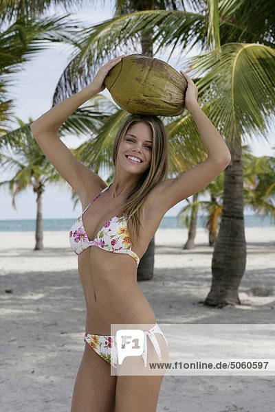 Woman at beach holding a coconut over her head