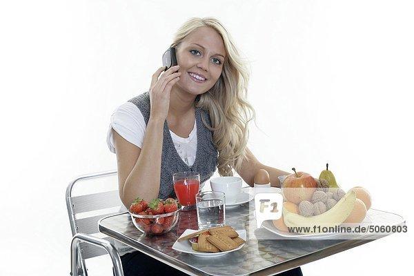 Frau dem Frühstück und Mobiltelefon verwenden
