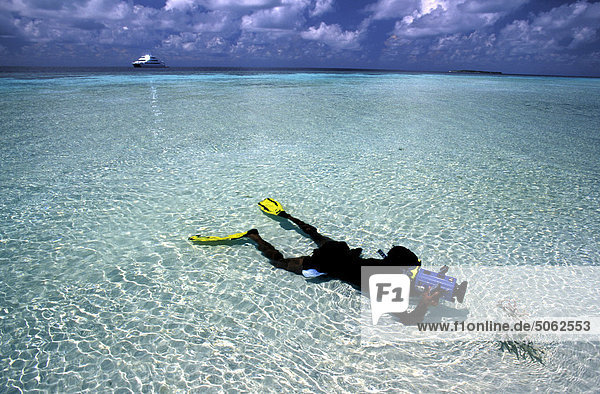 Maldives  diver with camera in shallow water