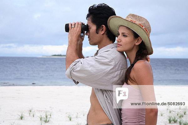 Maldives. Paar am Strand  Menschen auf der Suche durch Ferngläser
