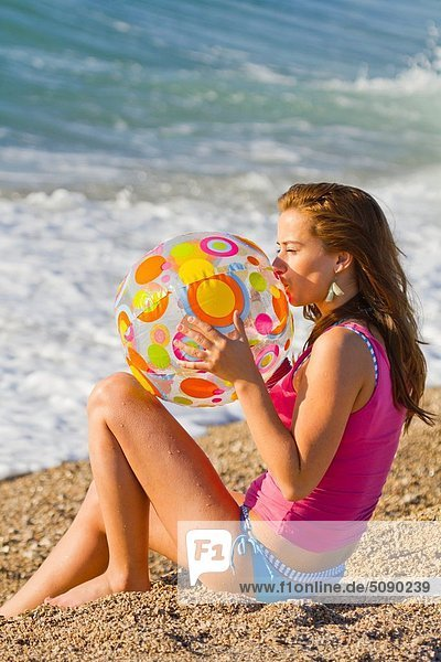 Attractive young woman is inflating a toy ball on the beach