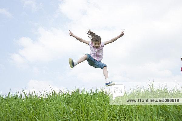 Mädchen springt auf einer Wiese