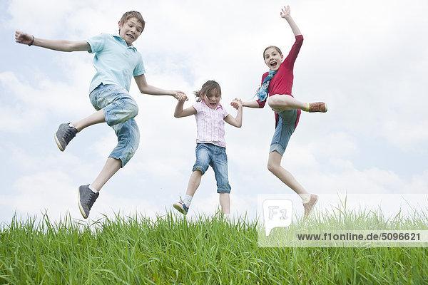Drei Kinder springen Hand in Hand auf einer Wiese