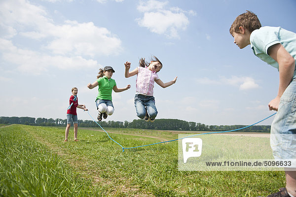 Four children skipping rope in meadow