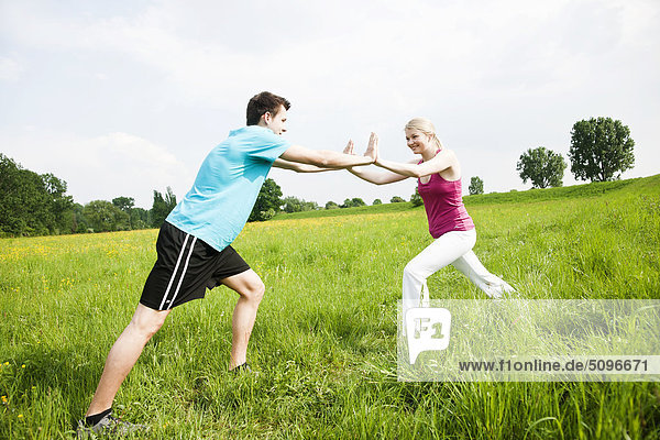 Junges Paar macht eine Dehnübung auf einer Wiese