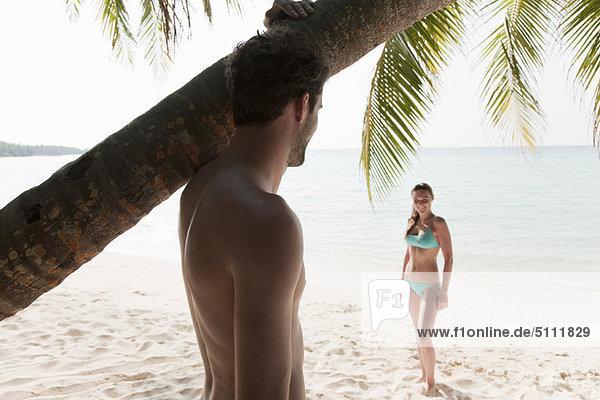 Man admiring woman on tropical beach