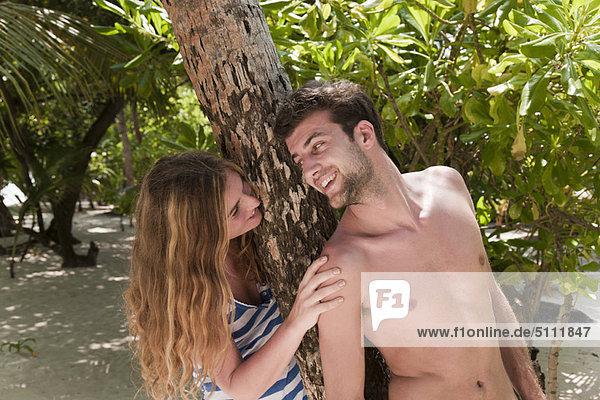 Couple talking under tree on beach
