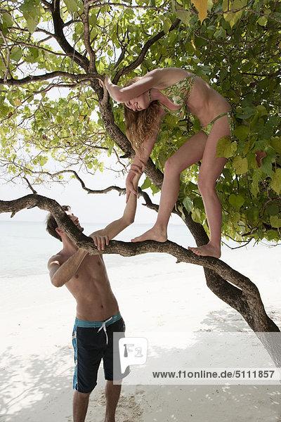 Woman climbing tree on tropical beach
