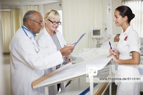 Ärzte mit Krankenschwester im Krankenhauszimmer