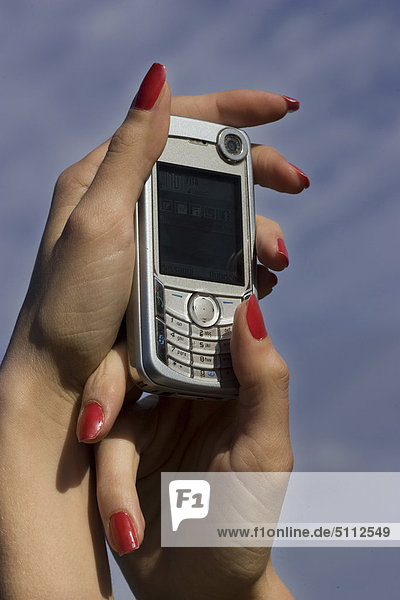 Woman's hand holding mobile phone