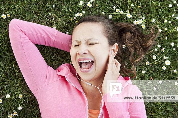 Frau singt zu Kopfhörern im Gras