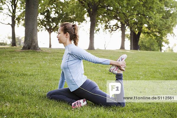 Frau streckt sich im Park