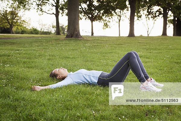 Frau im Park im Gras liegend
