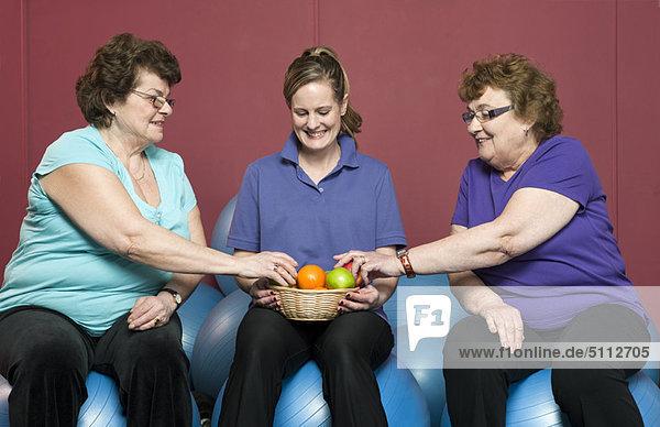 Ältere Frau mit Obst im Fitnessstudio