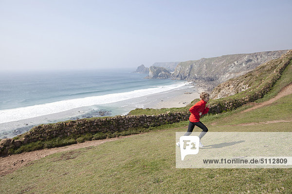 Boy running on cliffs over beach
