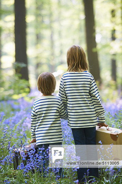 Kids with luggage in field of flowers