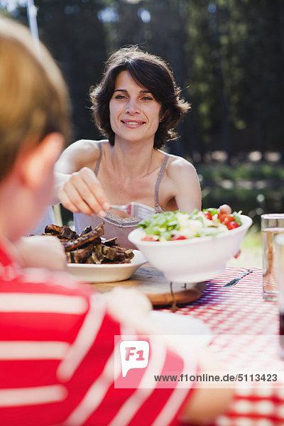 Mutter serviert Salat beim Picknick