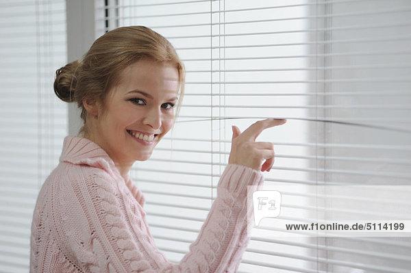 Lächelnde Frau schaut durch die Jalousien