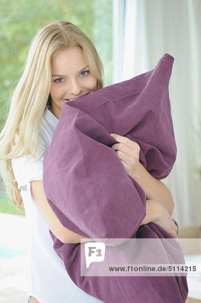 Frau umarmt Kissen zu Hause